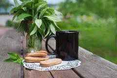 Copo preto do café da manhã, cookies, hortelã fotos de stock royalty free
