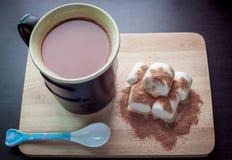 Copo preto e cacau quente com o marshmallow na terra traseira de madeira Imagens de Stock Royalty Free