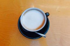 Copo quente do preto do café do cappuccino no fundo de madeira imagem de stock royalty free