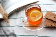 Copo transparente do chá com limão, pão estaladiço do centeio, um livro, luz natural, café da manhã foto de stock
