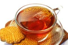 Copo transparente do chá e dos bolinhos Imagens de Stock