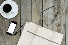 Copo vazio do jornal, do smartphone e de café na tabela de madeira foto de stock royalty free