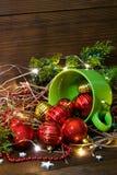 Copo verde com brinquedos e luzes do Natal no fundo de madeira foto de stock