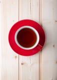 Copo vermelho com chá em pires fotografia de stock royalty free