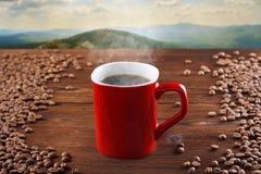 Copo vermelho do café quente em um fundo de madeira, em um fundo das montanhas Café de fumo, cozinhando imagens de stock
