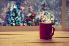 Copo vermelho do café quente na tabela de madeira no partido da noite de Natal Fotografia de Stock Royalty Free
