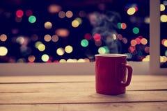 Copo vermelho do café quente na tabela de madeira no partido da noite de Natal Imagens de Stock Royalty Free