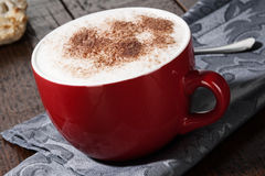 Copo vermelho do cappuccino Fotografia de Stock
