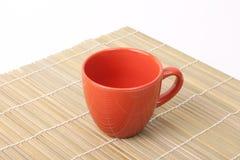 Copo vermelho no canto de bambu Fotos de Stock