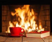 Copo vermelho, vidros e livro velho perto da chaminé na tabela de madeira Foto de Stock Royalty Free