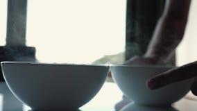 Copos brancos da sopa quente no fundo do sol Vapor quente de uma placa da sopa filme
