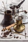 Copos brancos para o café de formas diferentes e de três fabricantes de café Grão do café e da colher em pires Fotografia de Stock Royalty Free