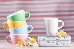 Copos coloridos com um jarro e um vintage dos narcisos amarelos retros Imagens de Stock Royalty Free