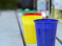 Copos coloridos descartáveis com bebidas Fotografia de Stock Royalty Free