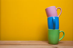 Copos de café coloridos na tabela de madeira sobre o fundo amarelo Fotos de Stock Royalty Free