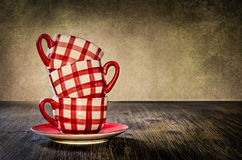 Copos de café coloridos na tabela no estilo do vintage Imagens de Stock