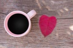 Copos de café com vista superior cor-de-rosa nas folhas de madeira coração do assoalho e do vermelho, vista superior Fotografia de Stock Royalty Free