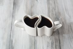Copos de café da forma do coração na tabela de madeira Fotografia de Stock