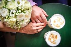 Copos de café das mãos do homem e da mulher na tabela Imagens de Stock