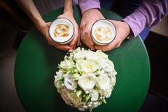 Copos de café das mãos do homem e da mulher na tabela Imagens de Stock Royalty Free