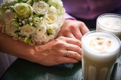 Copos de café das mãos do homem e da mulher na tabela Foto de Stock