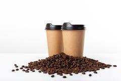 Copos de café do ofício e feijões de café no fundo branco imagem de stock