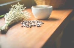 Copos de café, feijões de café e flores secadas em uma tabela de madeira Th fotografia de stock royalty free