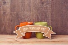 Copos de café na tabela de madeira com bandeira do cartão Celebração do dia da amizade Fotografia de Stock