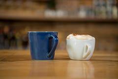 Copos de café na tabela de madeira no café Fotografia de Stock