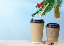 Copos de café de papel em um fundo de madeira do Natal da tabela Imagem de Stock Royalty Free