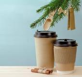 Copos de café de papel em uma tabela de madeira com refeição matinal da árvore de abeto Fotos de Stock