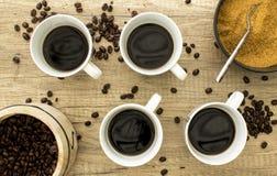 4 copos de café preto com feijões e açúcar na superfície de madeira da Imagem de Stock Royalty Free