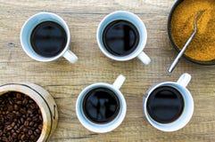 4 copos de café preto com feijões e açúcar na superfície de madeira da Fotografia de Stock Royalty Free
