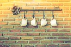 Copos de café que penduram nos ganchos na frente da parede de tijolo Fotografia de Stock