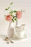 Copos de chá brancos e um vaso da flor Imagens de Stock Royalty Free