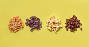 Copos de maíz bocado de los diversos cereales y pila de las palomitas en la opinión superior del fondo amarillo para el desayun fotos de archivo libres de regalías