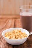 Copos de maíz cereal y chocolate caliente en la tabla de madera Foto de archivo
