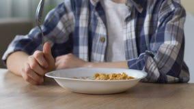 Copos de maíz con la leche para el desayuno sano, muchacho que come antes de la escuela, cierre para arriba metrajes