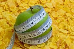 Copos de maíz con la manzana con la cinta de medición Fotografía de archivo libre de regalías