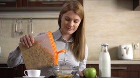 Copos de maíz de colada de la empresaria atractiva joven hermosa en un cuenco para el desayuno en la cocina almacen de metraje de vídeo
