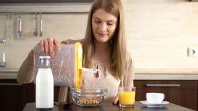 Copos de maíz de colada de la mujer atractiva joven hermosa en un cuenco para el desayuno en la cocina almacen de metraje de vídeo