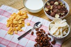 Copos de ma?z del desayuno y diversos cereales en taza del cuenco y de la leche en el fondo de madera para la comida sana del cer imágenes de archivo libres de regalías