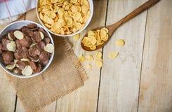 Copos de maíz del desayuno y diversos cereales en taza del cuenco y de la leche en el fondo de madera para la comida sana del cer fotos de archivo libres de regalías