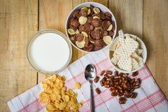 Copos de maíz del desayuno y diversos cereales en taza del cuenco y de la leche en de madera fotos de archivo libres de regalías