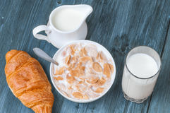 Copos de maíz en cuenco con leche y el vidrio de leche con el jarro en la tabla azul de madera Fotografía de archivo