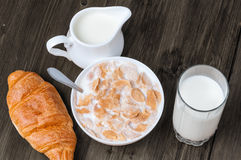 Copos de maíz en cuenco con leche y el vidrio de leche con el jarro en la tabla de madera rústica vieja Imagenes de archivo
