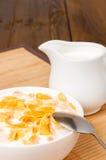 Copos de maíz en cuenco, jarro de leche y servilleta en la tabla de madera Fotografía de archivo libre de regalías