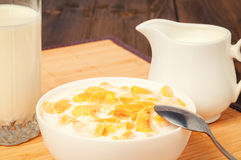 Copos de maíz en cuenco y el vidrio de leche en la tabla de madera Imagen de archivo