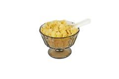 Copos de maíz en un bol de vidrio tradicional pardusco con el soporte y una mitad china blanca de la cuchara enterrada en los cop Imagen de archivo libre de regalías