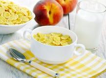 Copos de maíz, leche y melocotones imagenes de archivo